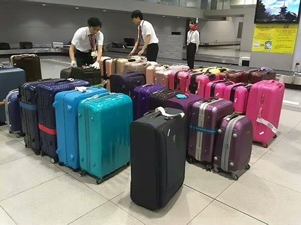 The airport staff sorts the luggage by color before putting it on the belt