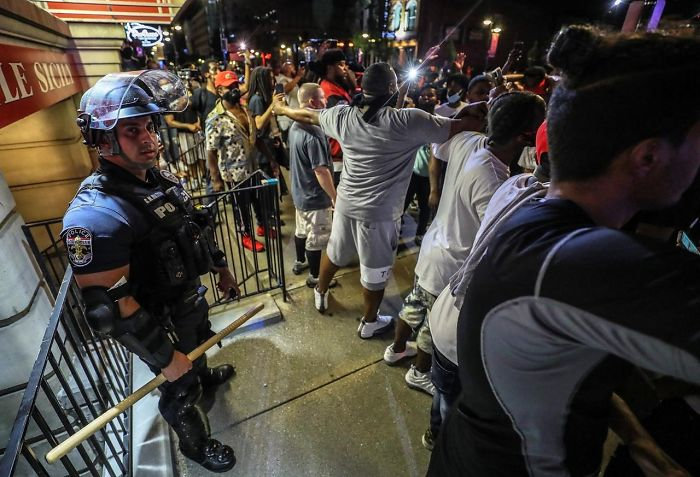 A Group Of Black People Protecting A Cop Who Got Separated From The Others