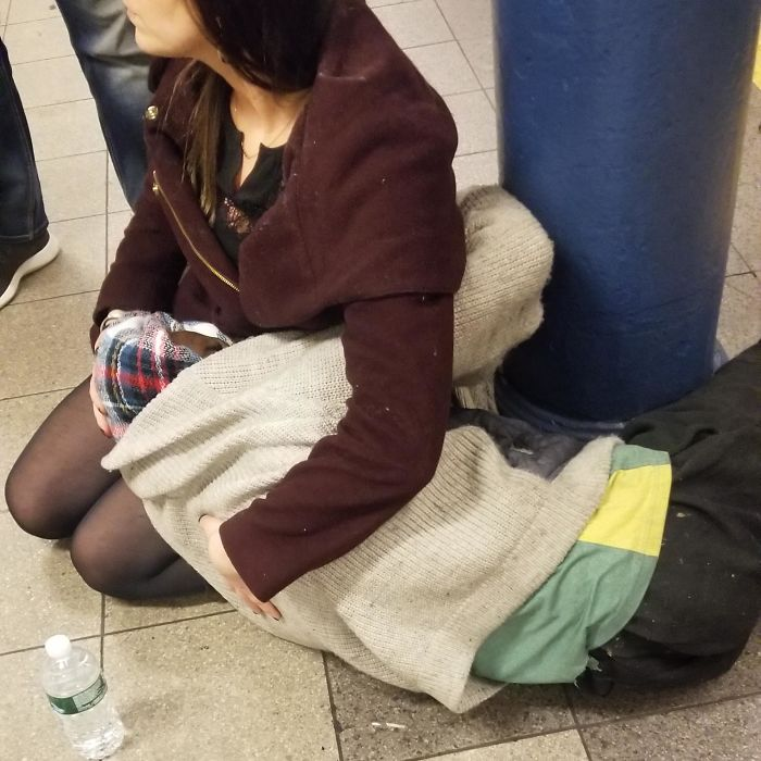 Woman Holds And Comforts A Homeless Man Experiencing Medical And Emotional Distress On The Subway Platform Until EMS Arrives
